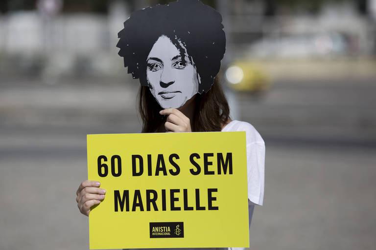Jovem usa máscara de Marielle em ato para lembrar os dois meses da morte da vereadora