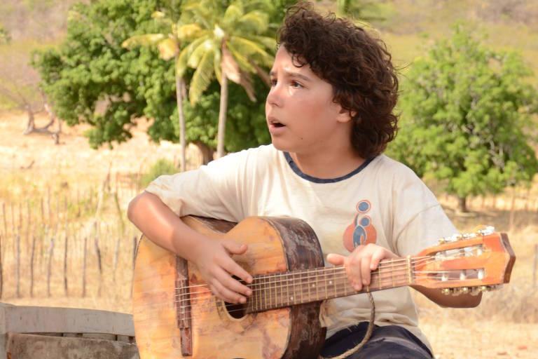 O ator Igor Jansen tocando violão