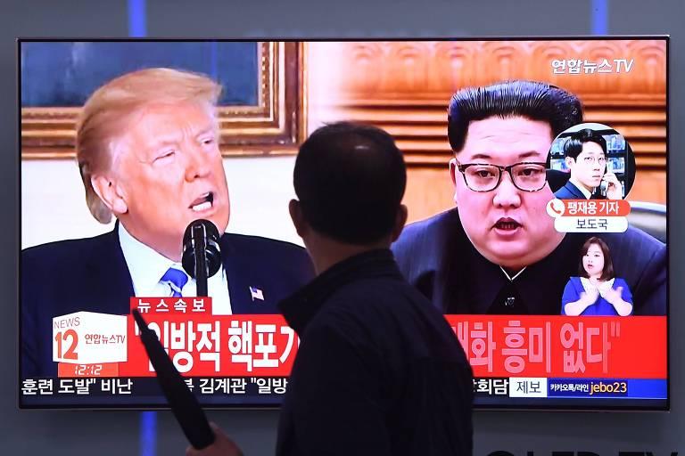 Homem observa TV com imagens de Donald Trump e de Kim Jong-un em Seul nesta quarta (16)
