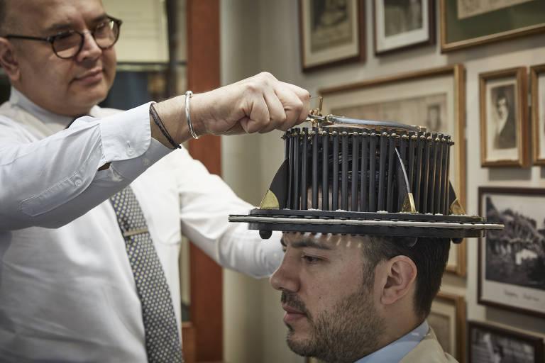 Homem mede cabeça de outro homem, que usa chapéu