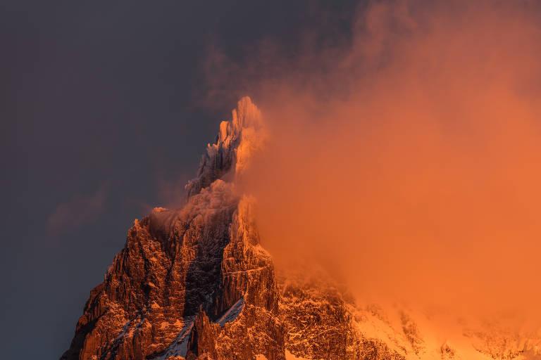 Detalhe de cume de montanha, parcialmente coberto por neve e por uma nuvem fina, que passa à sua frente. A nuvem e o cume estão refletidos por uma luz alaranjada do sol