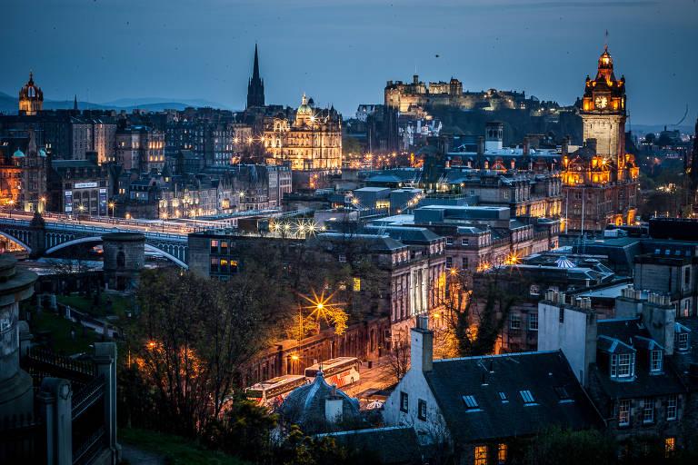 Vista da parte antiga da capital escocesa, com o castelo de Edimburgo ao fundo, no alto do morro, e a torre do relógio do hotel Balmoral, à direita