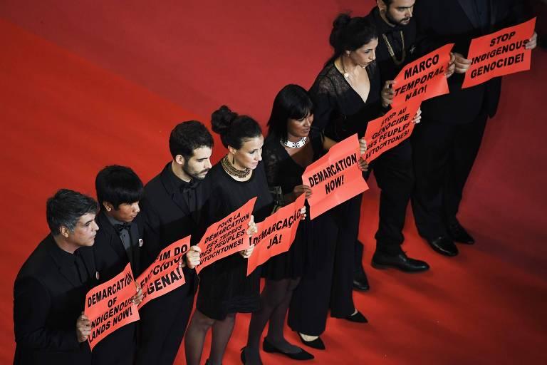"""A equipe de """"Chuva É Cantoria na Aldeia dos Mortos"""" empunha cartazes pedindo demarcação e contra o genocídio indígena no tapete vermelho de Cannes"""