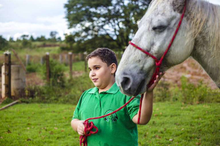 Gabriel Ottoni, 10, e o cavalo Pé de Pano, que são cegos, na associação Sonho Meu em Sorriso (MT)