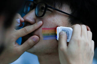 A participant applies rainbow coloured facepaint before a 5.17 km run to mark International Day Against Homophobia in a park in Beijing