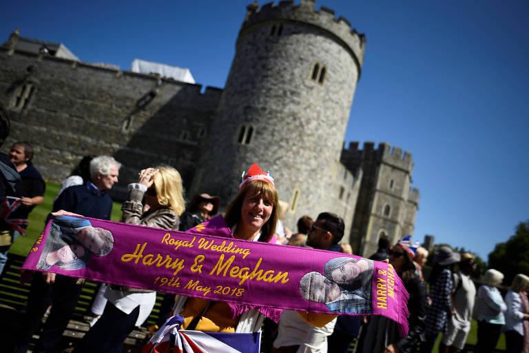 Mulher segura faixa comemorativa do casamento real durante ensaio da cerimônia em Windsor