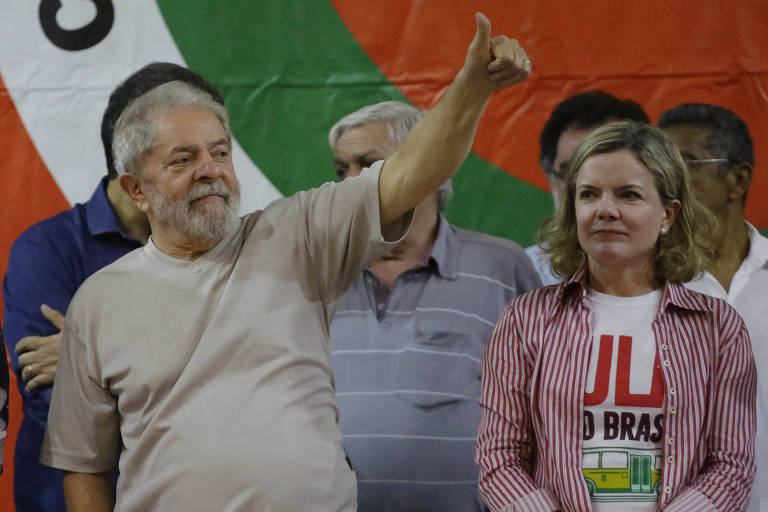 Lula fazendo sinal positivo com a mão com Gleisi ao seu lado