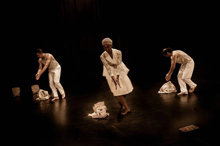 pessoas dançando em volta de pilhas de roupa