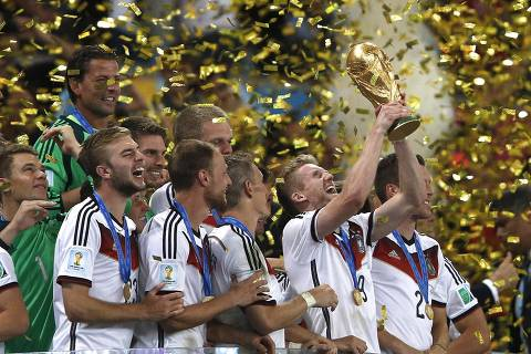 TOPSHOTS  -- AFP PICTURES OF THE YEAR 2014 --  Germany's forward Andre Schuerrle (C) holds the trophy as he celebrates with teammates after his team's victory in the final football match between Germany and Argentina for the FIFA World Cup at The Maracana Stadium in Rio de Janeiro on July 13, 2014.   AFP PHOTO / ADRIAN DENNIS ORG XMIT: FK3727