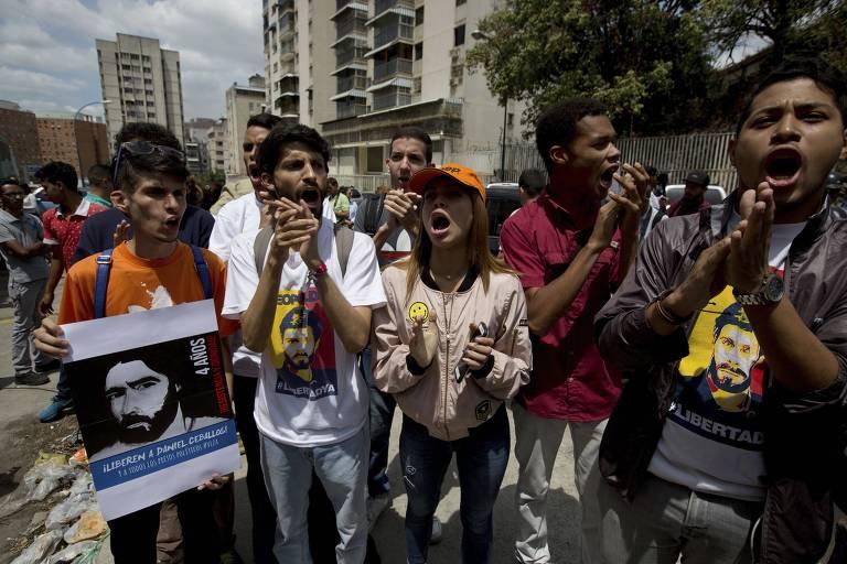 Grupo de ativistas carrega cartazes com fotos do ex-prefeito Daniel Ceballos, um dos presos políticos, batem palmas e gritos; das cinco pessoas que aparecem à frente na imagem, três delas usam camisetas com a imagem do ex-prefeito Leopoldo López com as cores da bandeira da Venezuela