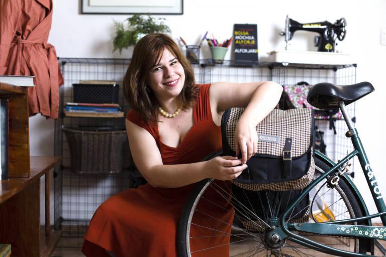 A empresária Priscila Moreno, ao lado de uma bicicleta, mostra um dos alforjes à venda pela marca