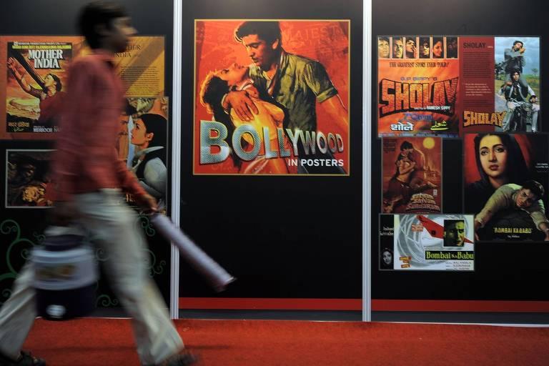 homem passa em frente a cartazes