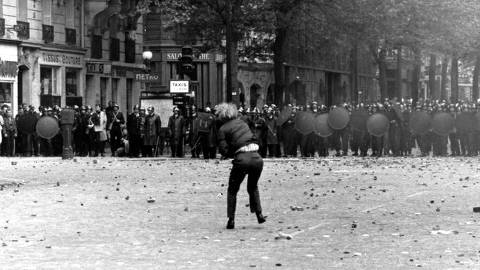 FILE - In this May 1968 file photo, a demonstrator hurls a stone to riot police officers in this May 1968, in Paris. The 50th anniversary of France's biggest revolt since World War II is sparking more enthusiasm in arts and intellectual circles, though, with a series of exhibitions staged in Paris. (AP Photo, Files) ORG XMIT: XPAR104