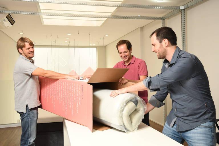 Os sócios Andreas Burmester, Ilan Vaserman e Amit Eiles, da Zissou, embalando um dos colchões compactos na sede da empresa em São Paulo