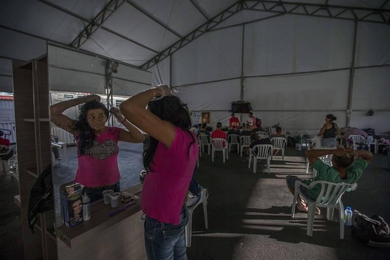 Em tenda de atendimento da Prefeitura de SP, frequentadores da cracolândia comem, dormem, assistem TV e cortam cabelo