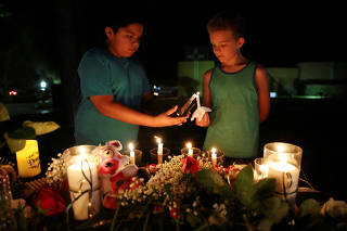 Attendees light a candle during a vigil for the victims of a shooting at Santa Fe High School that left several dead and injured in Santa Fe, Texas