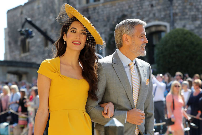 George e Amal Clooney chegam ao Castelo de Windsor para a cerimônia de Meghan e Harry. A advogada usa um vestido amarelo com chapéu da mesma cor. O ator veste um terno cinza.