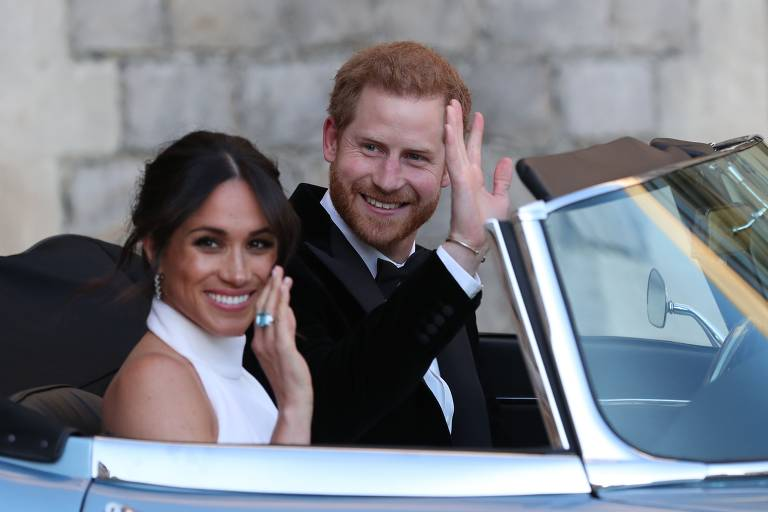 Príncipe Harry e Meghan Markle acenam ao sair de Jaguar para a recepção de casamento em Frogmore