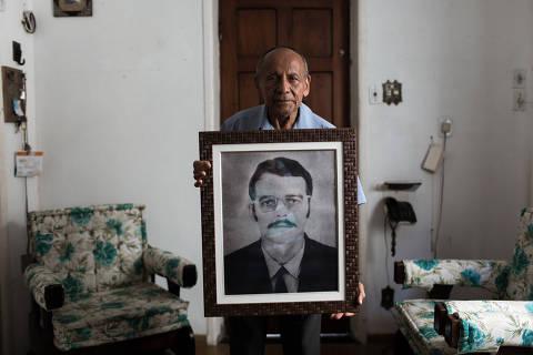 Rio de Janeiro, Rj, BRASIL. 17/05/2018; Sebastião Braz, segura um retrato de Stuart Angel que chegou a abrigar em sua casa durante a ditadura -   ( Foto: Ricardo Borges/Folhapress)