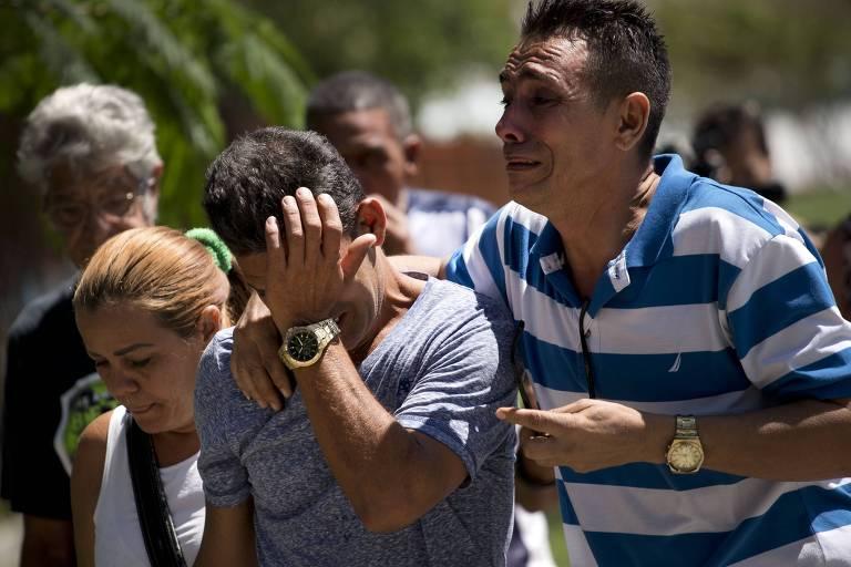 Três pessoas aparecem à frente da imagem: à esquerda, uma mulher loura de cabelo preso com camiseta branca e com a alça preta de uma bolsa pendurada de cabeça baixa; a seu lado, um homem de camiseta cinza passa a mão no rosto como sinal de que está chorando e que é segurado à direita por outro homem, de camisa pólo listrada azul e branca que também chora; ao fundo deles, outros dois homens aparecem à distância