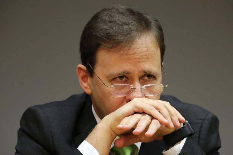 Retrato de homem que olha por cima de óculos apoiados na ponta do nariz; ambas as mãos estão cruzadas sobre sua boca; olhar demonstra apreensão.