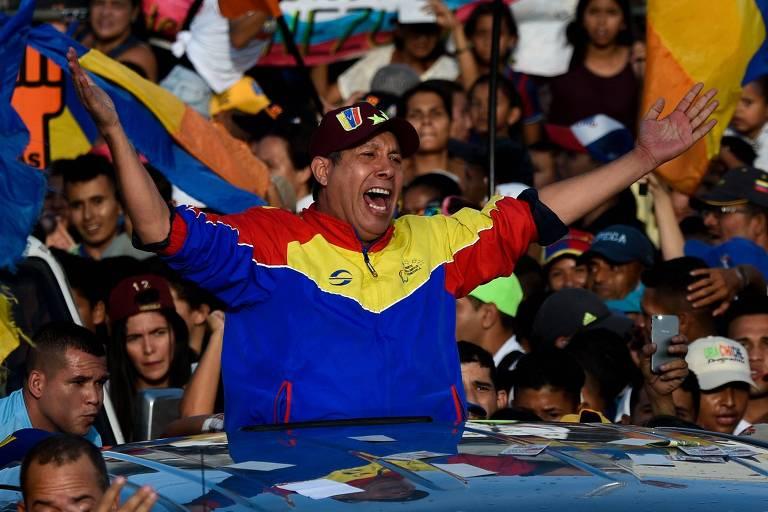 Com casaco azul, amarelo e vermelho, as cores da bandeira da Venezuela, Henri Falcón aparece de braços abertos e boca aberta, como se estivesse gritando, enquanto está na caçamba de uma camionete, da qual só se vê o teto na imagem; ao fundo centenas de pessoas, algumas com bandeiras laranjas e azuis, do Partido Avanço Progressista