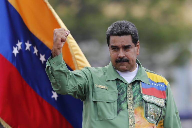 Maduro aparece sério, com uma camisa verde com a bandeira da Venezuela do lado esquerdo e levantando a mão direita em riste; ao lado esquerdo dele, uma bandeira da Venezuela