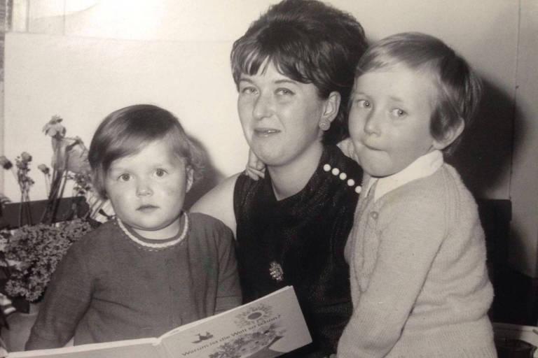 Vestida de preto, mãe está com livro na mão direita; as crianças estão de casaco, sendo Katrin sentada e o irmão em pé; imagem em preto e branco