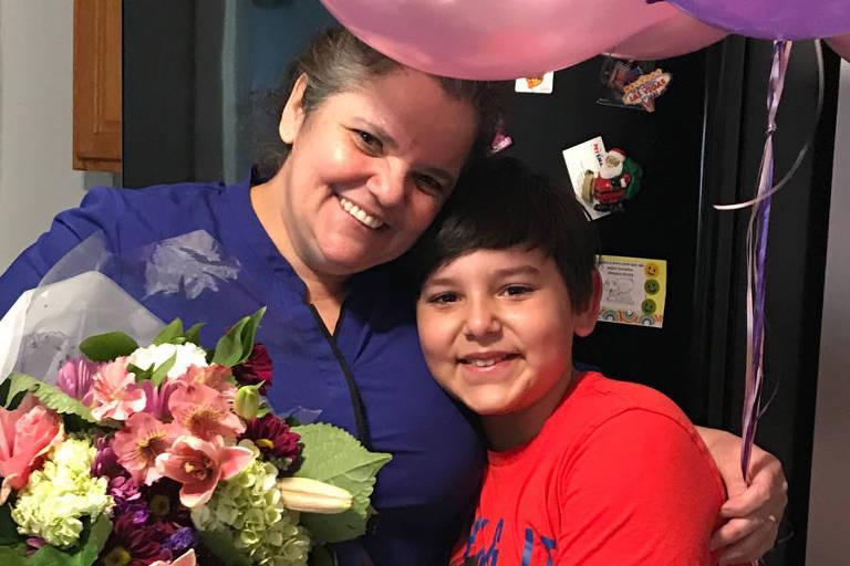 De camisa roxa, Lucimar aparece sorrindo com um buquê de flores vermelhas, verdes e amarelas nas mãos, e é abraçada pelo filho, que está de camiseta vermelha; ela também segura dois balões de festa: um roxo e outro rosa; ao fundo, uma estante
