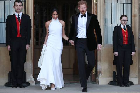 TOPSHOT - The newly married Britain's Prince Harry, Duke of Sussex, (R) and Meghan Markle, Duchess of Sussex, (L) leave Windsor Castle in Windsor on May 19, 2018 after their wedding to attend an evening reception at Frogmore House.  / AFP PHOTO / POOL / Steve Parsons ORG XMIT: ROYALWedding193596.JPG