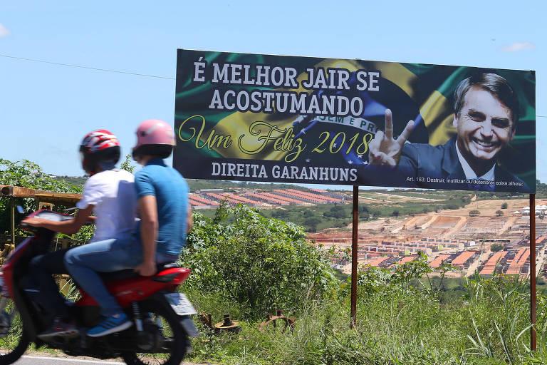 """Outdoor com foto de Jair Bolsonaro sobre fundo da bandeira brasileira, onde se lê """"é melhor jair se acostumando - direita Garanhuns"""". Uma moto vermelha passa na estrada em frente ao outdoor, com duas pessoas montadas."""