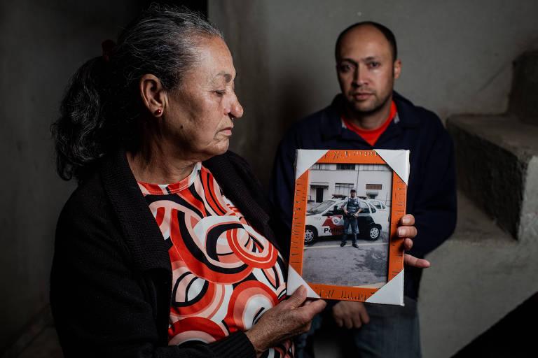 Gedalva, 66, ao lado do filho Gilmar, 41, com a foto de seu outro filho, Osmar, PM morto em 2012