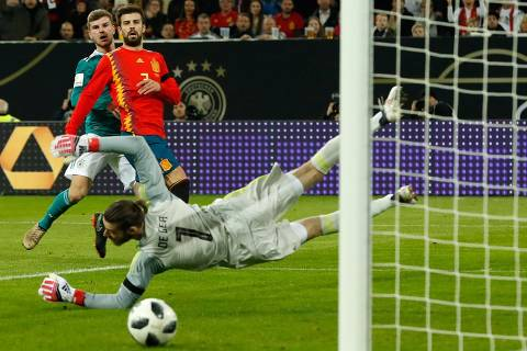 Spain's goalkeeper David de Gea (R) jumps to fend off a ball shot by Germany's striker Timo Werner (L) during the international friendly football match of Germany vs Spain in Duesseldorf, western Germany, on March 23, 2018, in preparation of the 2018 Fifa World Cup. / AFP PHOTO / Odd ANDERSEN