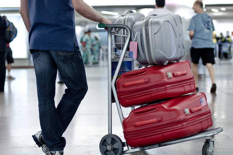 Homem segura carrinho de malas com três malas empilhadas