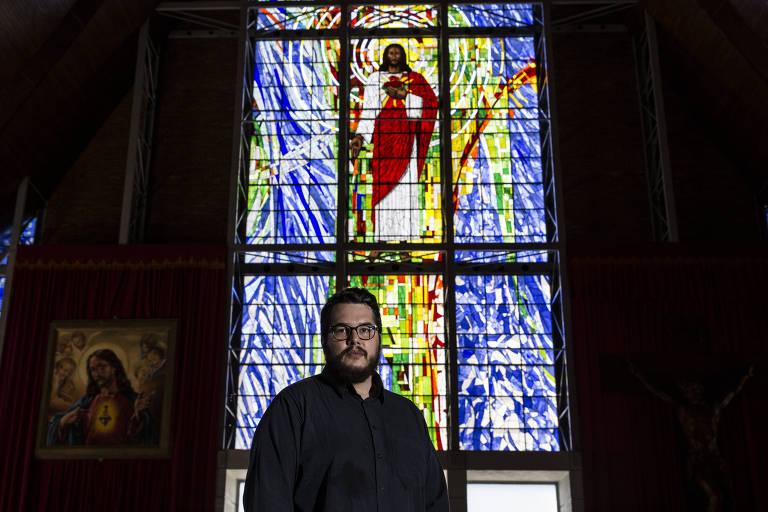 Bernardo Pires Küster, youtuber que acusa a cúpula da CNBB de ser esquerdista, em frente a um vitral que reproduz a imagem de Jesus Cristo