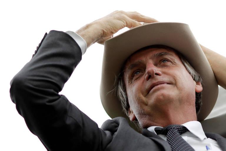 Em evento em abril contra o ex-presidente Lula, Jair Bolsonaro experimenta chapéu dado por apoiadores