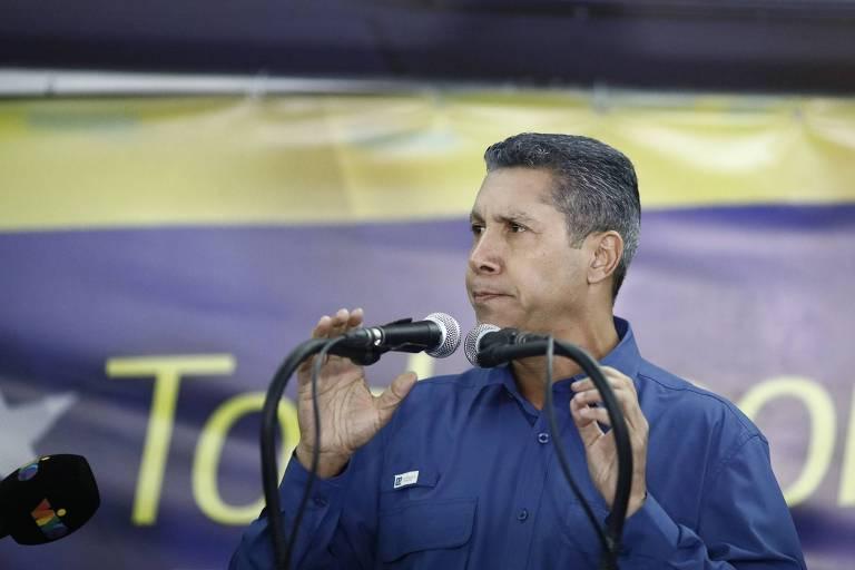 Falcón segura pedestais de dois microfones enquanto olha para a direita; ao fundo, parte de um painel com a bandeira da Venezuela