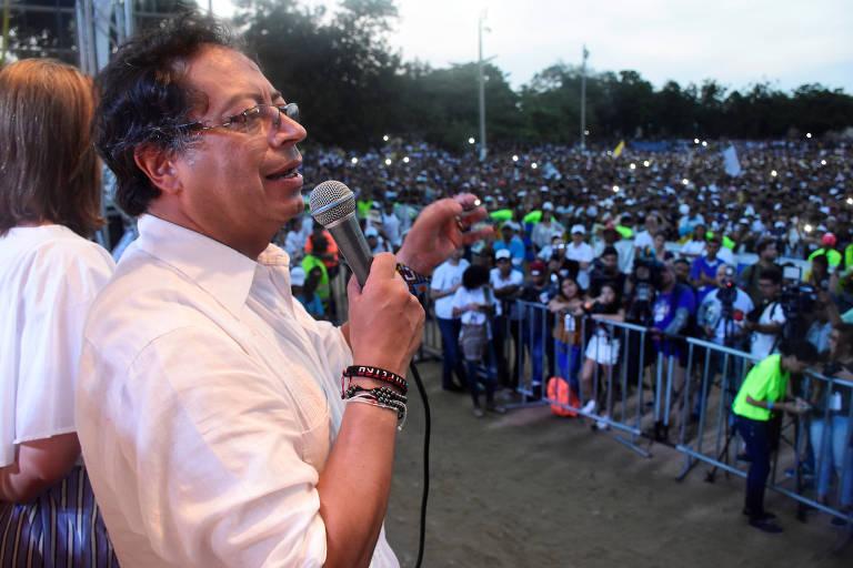 De camisa bege, Petro segura um microfone com fio em um palco; ele aparece de lado; à direita, milhares de apoiadores o acompanham