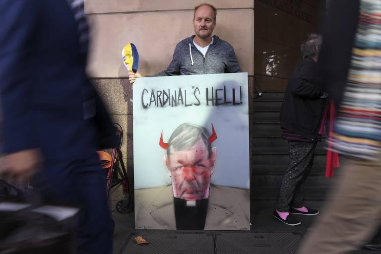 Pell é retratado em desenho no cartaz com chifres de diabo e a troca de seu sobrenome para hell (inferno, em inglês); quadro é segurado por um homem que está na parede de um tribunal