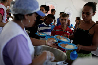 Venezuelans line up to receive food at the Casa de Acolhida Santa Catarina shelter in Manaus