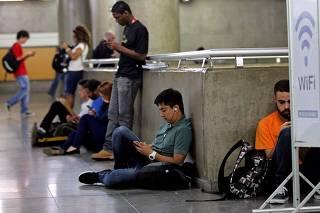 Pessoas usam laptop na estação Sé Metrô