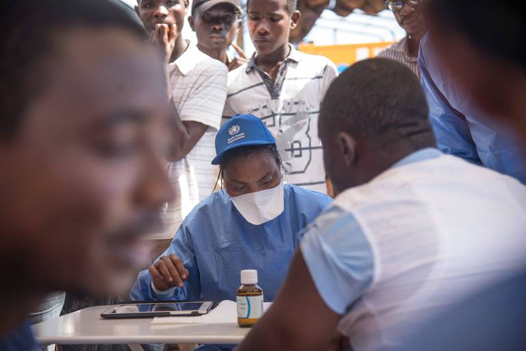 Sentada a uma mesa, enfermeira vestida de azul com máscara cirúrgica conversa ao fundo com um homem vestido de camiseta azul e colete branco; à frente, homem espera em fila