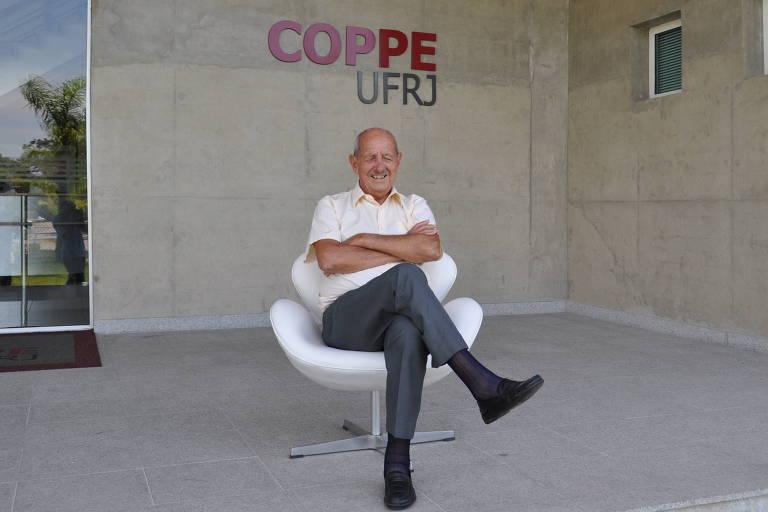 Alberto Luiz Galvão Coimbra sentado em uma cadeira; atrás, o letreiro da Coppe Ufrj