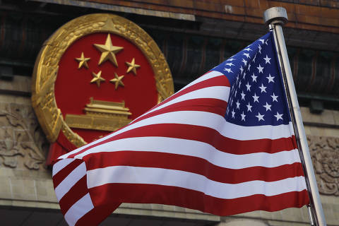FILE - In this Nov. 9, 2017, file photo, an American flag is flown next to the Chinese national emblem during a welcome ceremony for visiting U.S. President Donald Trump outside the Great Hall of the People in Beijing. The State Department said an email notice Wednesday, May 23, 2018, that a U.S. government employee in southern China reported abnormal sensations of sound and pressure, recalling similar experiences among American diplomats in Cuba who later fell ill. (AP Photo/Andy Wong, File) ORG XMIT: XBEJ101
