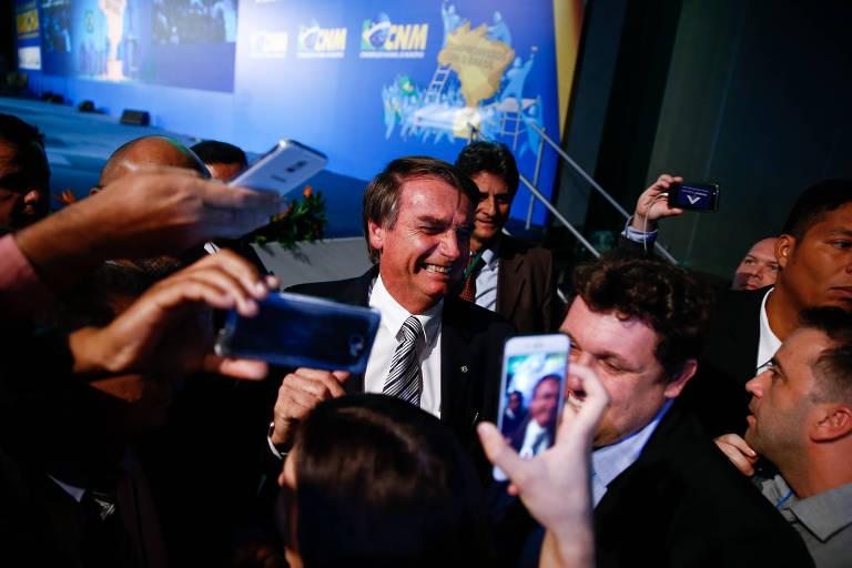 O pré-candidato à Presidência da República Jair Bolsonaro (PSL) sorri ao ser fotografado por celulares durante sabatina realizada pela CNM (Confederação Nacional dos Municípios), em Brasília