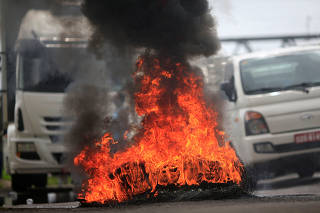 Burning tyres are seen as truck owners block the BR-324 highway during a protest against high diesel prices in Simoes Filho near Salvador