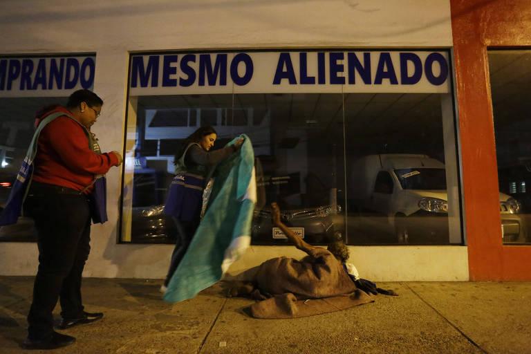 Funcionária da Prefeitura de São Paulo entrega cobertor a morador de rua que se recusa a ir para um abrigo