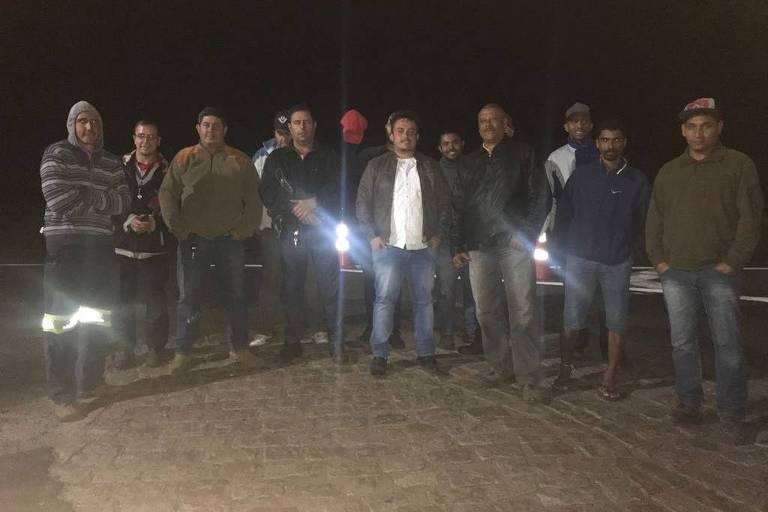 12 homens em pé posam para foto com lanternas nas mãos
