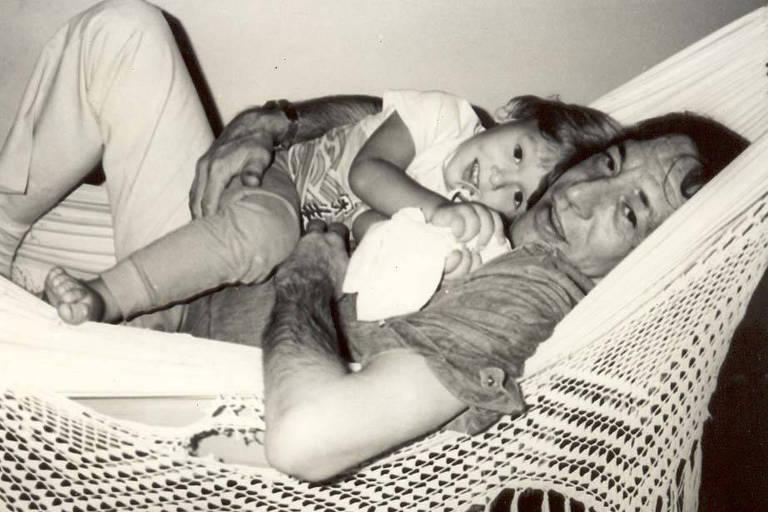 pai e filho sorriem deitados juntos e abraçados em uma rede