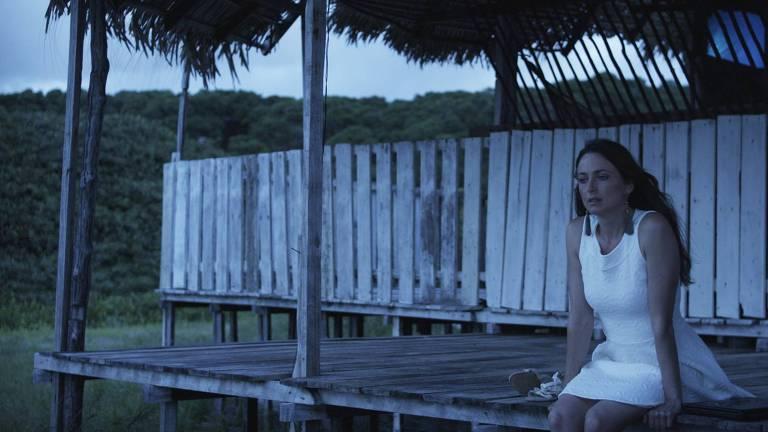 A atriz Lorena Lobato está sentada com um vestido branco